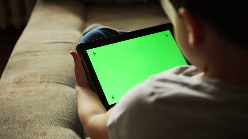Child using a digital tablet PC with green screen, back view