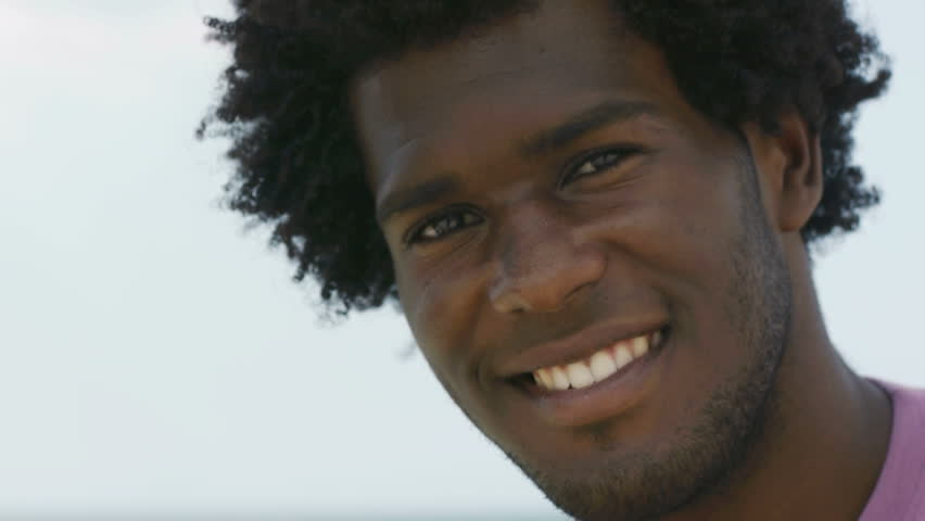 Portrait of young african american man looking at camera near the sea. Head and shoulders, copy space