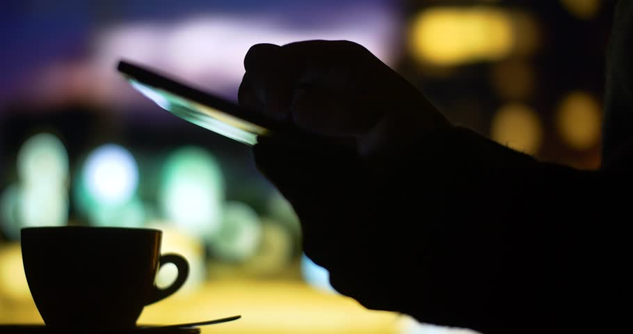 Drinking coffee tea close up of business man's hand using green screen tablet computer pc to check internet stock market exchange trading news in coffee shop cafe with a city night bokeh background
