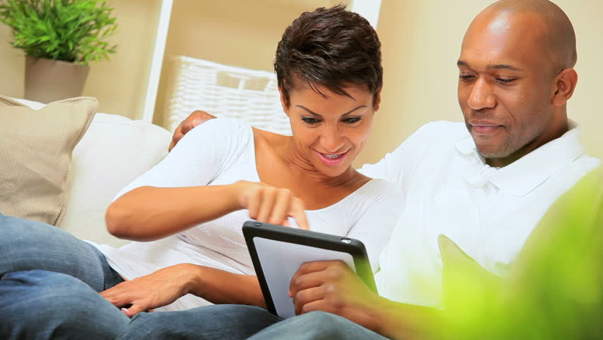 Young african-american couple relaxing on home sofa & using a wireless tablet