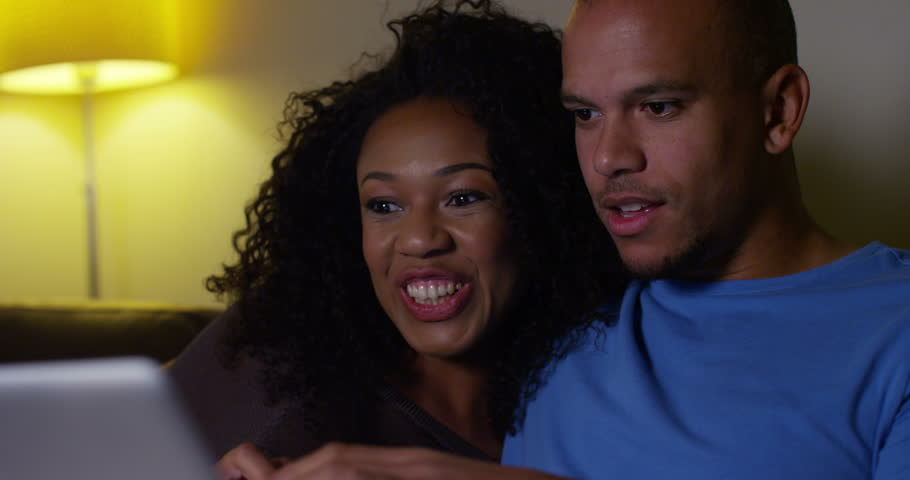 An attractive African American couple watching a movie on a laptop. Shot on RED Epic. | Shutterstock HD Video #11704355
