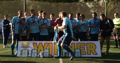 YAROSLAVL, RUSSIA - SEPTEMBER 12 : amateur soccer players team group celebrating the victory and become champion of game while holding win coup on September 12,  2015 in Yaroslavl RUSSIA
