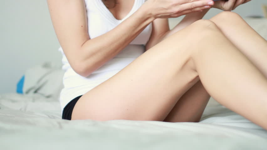 Woman applying moisturizer cream on her leg
