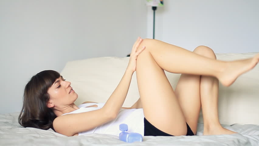 Woman lying on bed and applying moisturizer cream on her leg