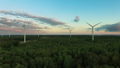 Aerial drone shot of wind turbines in the forest near the sea at sunset. Shot in 4K (UHD).