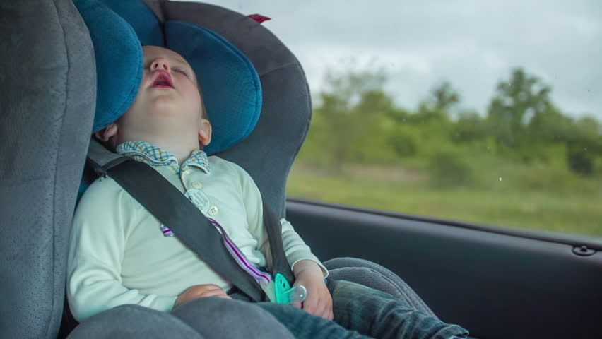 In this video you can see a child sleeping in a child seat on the back of the chair in the car.