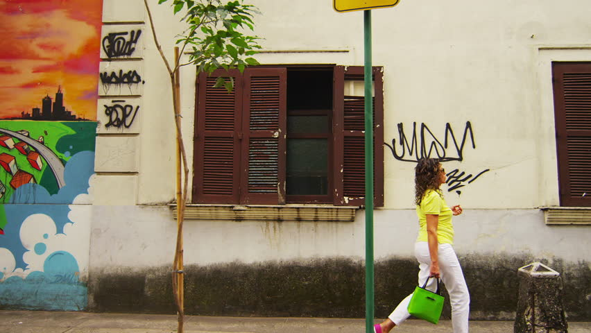 RIO DE JANEIRO - CIRCA JUNE 2013: Slow tracking down a street where people can be seen walking next to a wall full of graffiti
