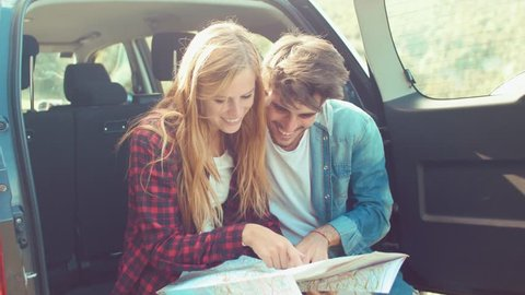 Handheld shot of couple sitting in car trunk checking map