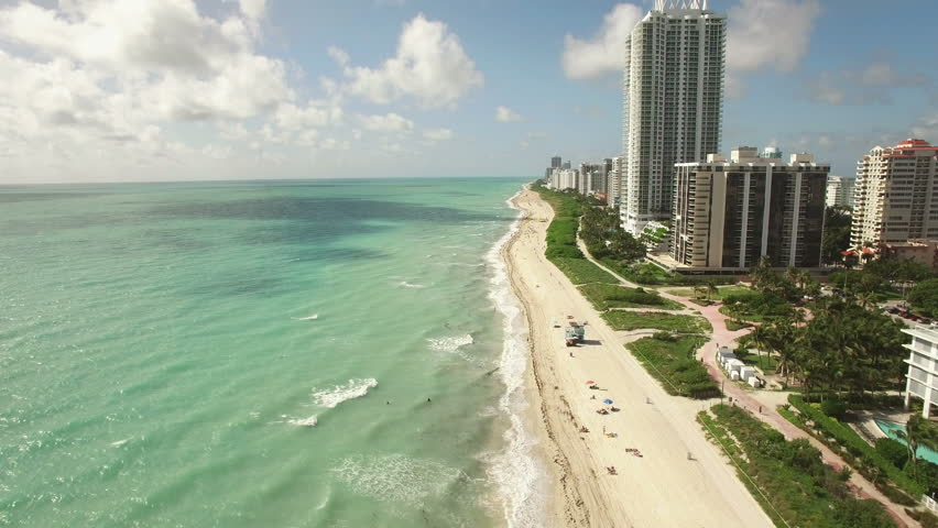 Aerial video of the waterfront, Miami Beach, 60th Collins Avenue. 4K Ultra HD. Shooting the video along the coastlines .