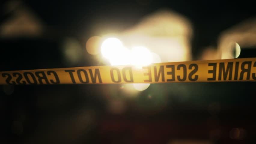 Crime scene tape blowing in a slight breeze around a real crime scene.