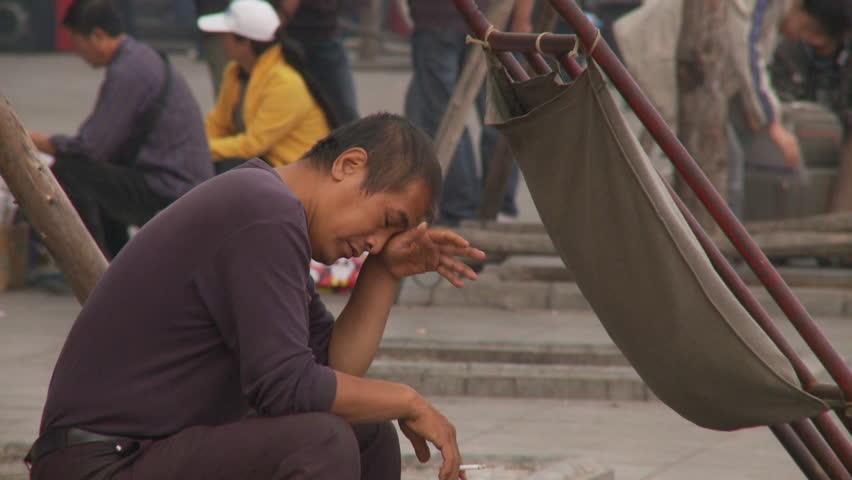 Dalian, China - October 2009: Chinese man sitting and smoking a cigarette in Dalian, China. #11784515