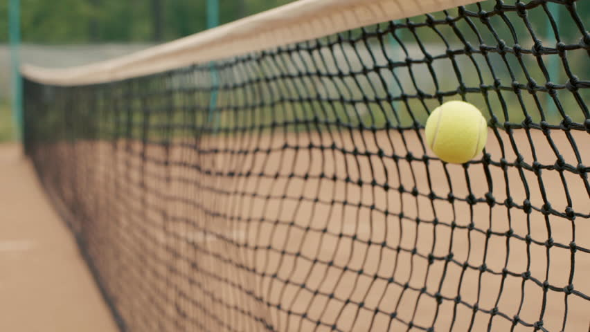 Yellow-green tennis ball stuck in the grid on red clay courts. Small depth of field #11810816
