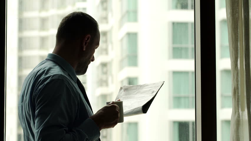 Young businessman reading newspaper and drinking coffee by the window in office  | Shutterstock HD Video #11813195