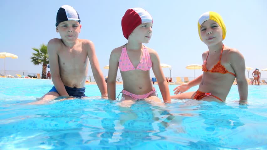 The boy and two girls sitting in the pool, girl pushed boy and then boy pushed girl