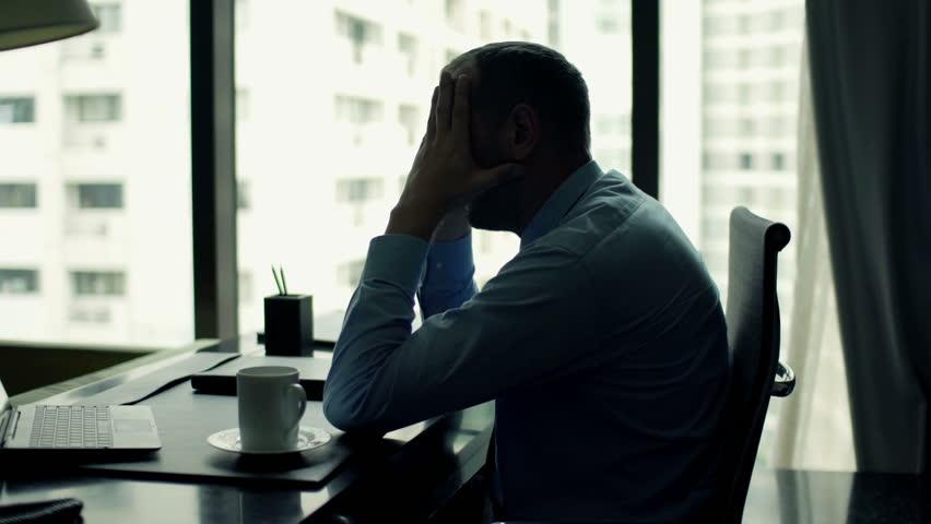 Sad, tired businessman sitting by desk in office  | Shutterstock HD Video #11827325