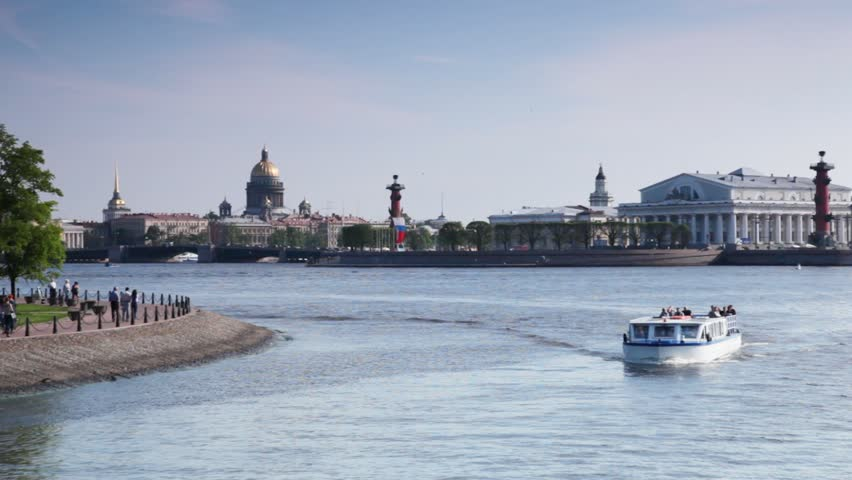 boat with passengers floats near Strelka Vasilievsky island on Neva in afternoon
