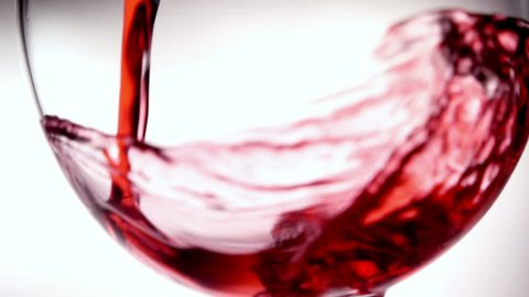 Pouring red wine into goblet in slow motion
