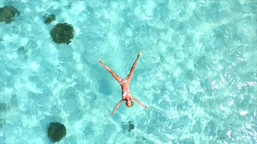AERIAL SLOW MOTION: Beautiful young woman swimming, lying on a water surface in crystal clear ocean