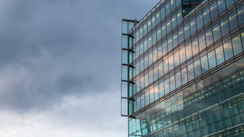 BERLIN, GERMANY – June 15, 2015: cloudy sky with modern illuminated reflected glass  facade timelapse Modern office building, pattern with reflect a sunset in the evening | Shutterstock HD Video #11930210