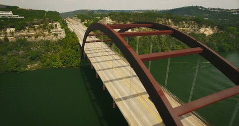 Aerial footage of the 360 bridge over a lake. The camera rotates around one of the sides of the bridge and over the road.
