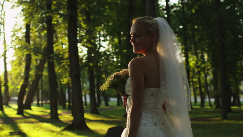 Bride is throwing a flower bouquet at wedding in a sunny park. Shot on RED Cinema Camera in 4K (UHD).