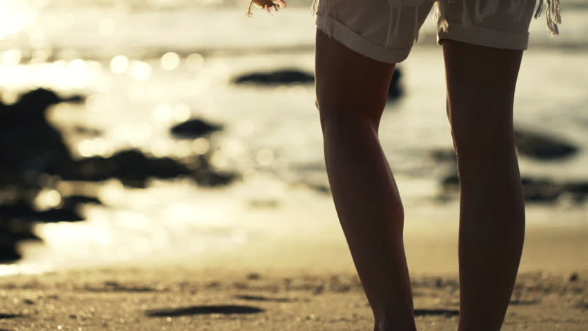 Young woman walking with flower close to the sea during sunset, slow motion, shot at 240fps
