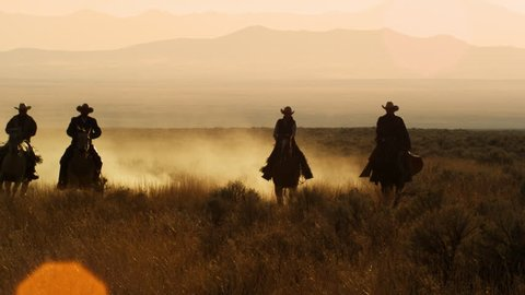 Slow motion silhouette shot of four cowboys galloping together in a line, Dusk kicks up as they ride.
