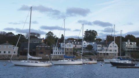 Boston, Massachusetts - September, 2012: Shot of boats moored in Rockport Harbor and homes on the far shore of the harbor. Rockport, Massachusetts.