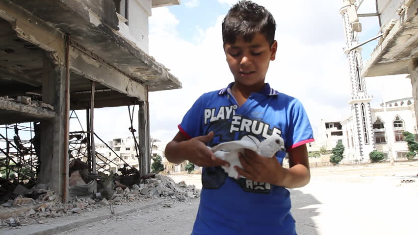 Syria, Homs, September 2013. A boy holding a white dove in the Syrian city of Homs