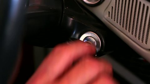 Man turns the key in the ignition lock of the old retro car close up