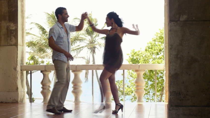 Young hispanic couple dancing latin american dance outdoors, dancers during exhibition