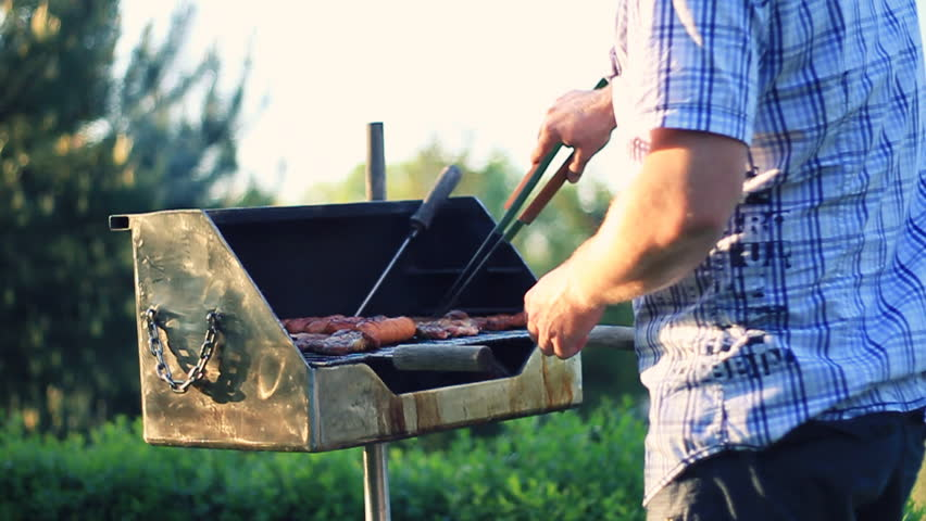 Man cooking meat on the barbecue grill, outdoors, camera stabilizer shot