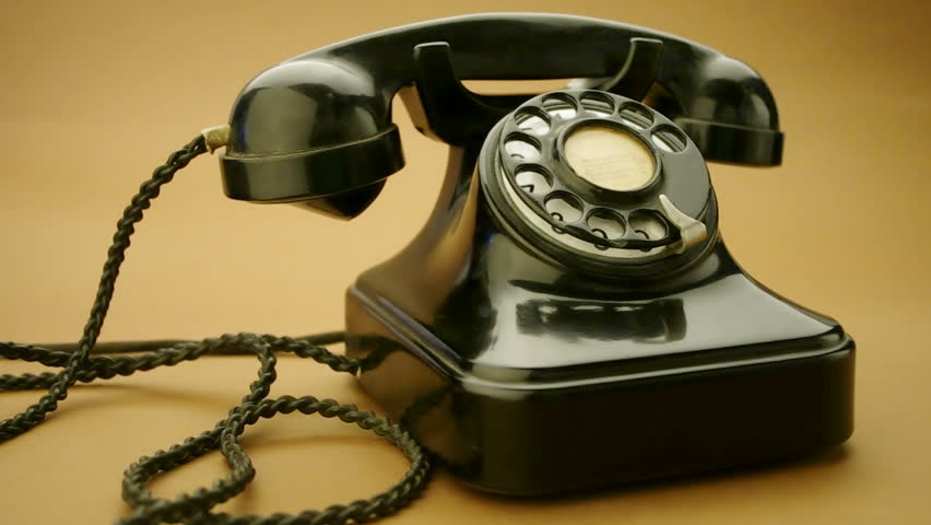 male hand on very old telephone on brown background