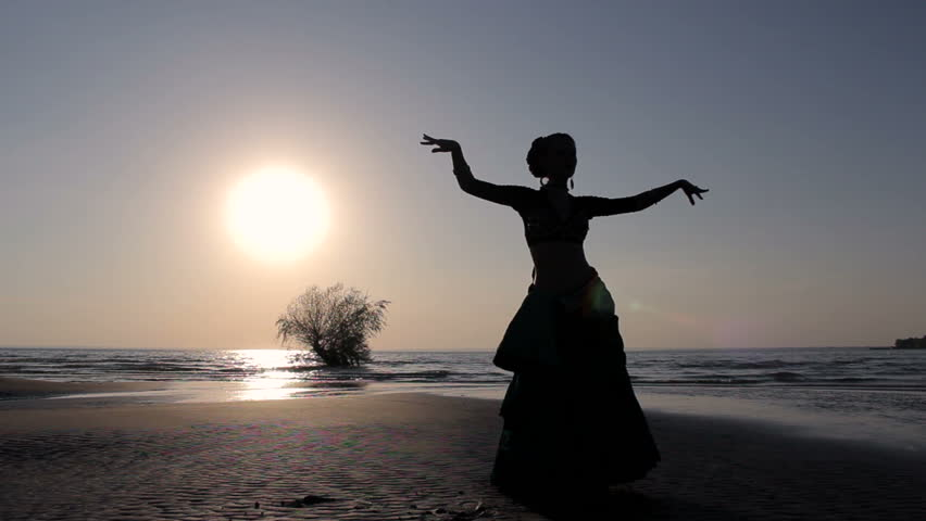 Silhouette girl oriental dancer masterly performing a dance on sunset