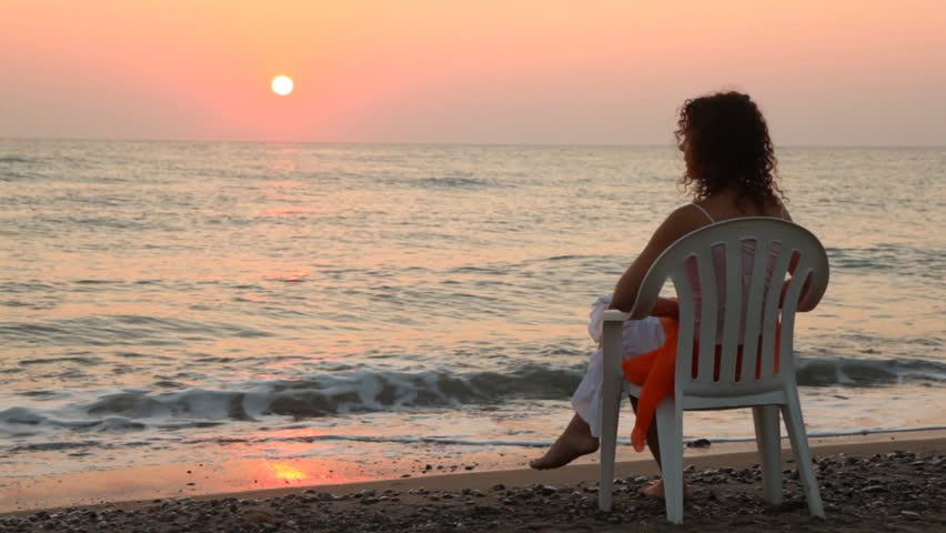curly-headed woman sits on white plastic chair alone on beach faced to sea at sunset