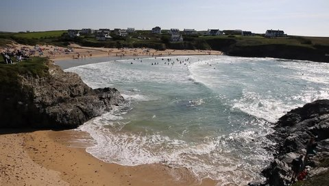 Many people swimming in waves Treyarnon Bay Cornwall England UK Cornish north coast between Newquay and Padstow on a sunny summer blue sky day