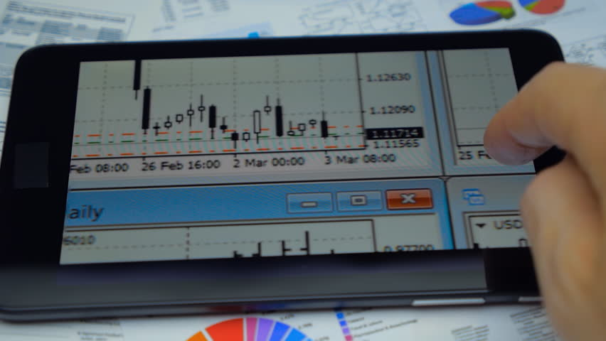 Financial analyst looking at the tablet in the Forex currency charts. Closeup. Shallow depth of field. Macro. The camera moves around
