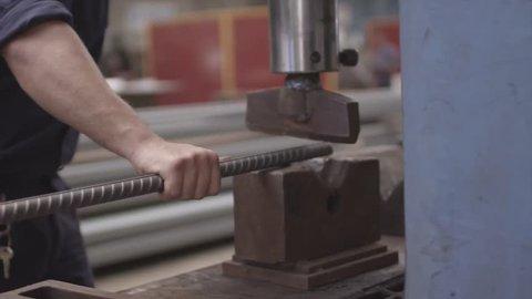 Steelworker uses industrial press to bend steel bar (rebar)