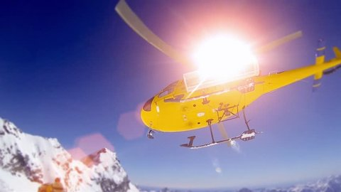 Action sportlers were dropped by a helicopter at the top of the mountains. The sun is shining brightly in the blue sky. There is a mountain range in the background covered in snow.