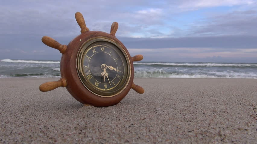 Ship Steering Wheel Like Clock On The Beach In Sand