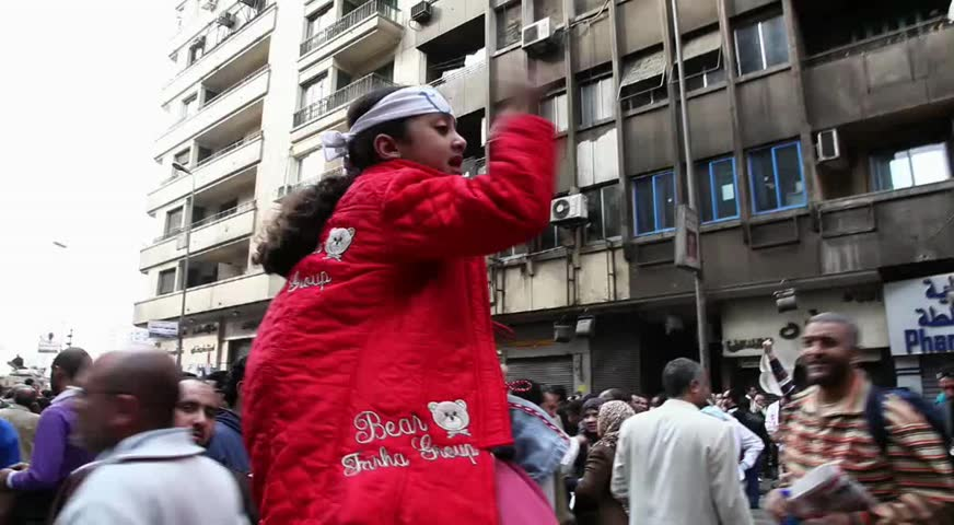 CAIRO - CIRCA JAN 2011: Small girl guides protesters in Tahrir Square circa January 2011, Cairo, Egypt. Tahrir Square was the focal point of the 2011 Egyptian Revolution where demonstrations grew to 250,000 plus people by day 6, January 31, 2011.