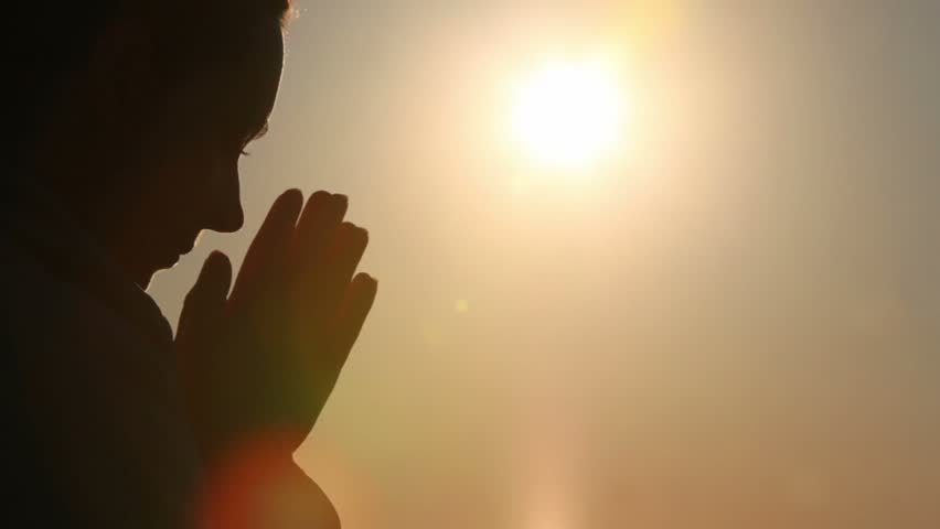 Silhouette of woman head with sunshine behind, holding hand in namaste | Shutterstock HD Video #1222375