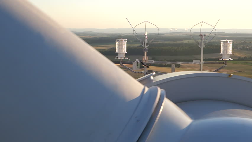 Wind turbines create renewable energy in Germany. Cooling tower of nuclear power plant in background.