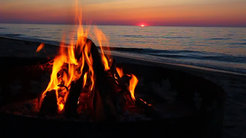 Campfire burns brightly at sunset along the beautiful beach of Lake Superior in northern Michigan