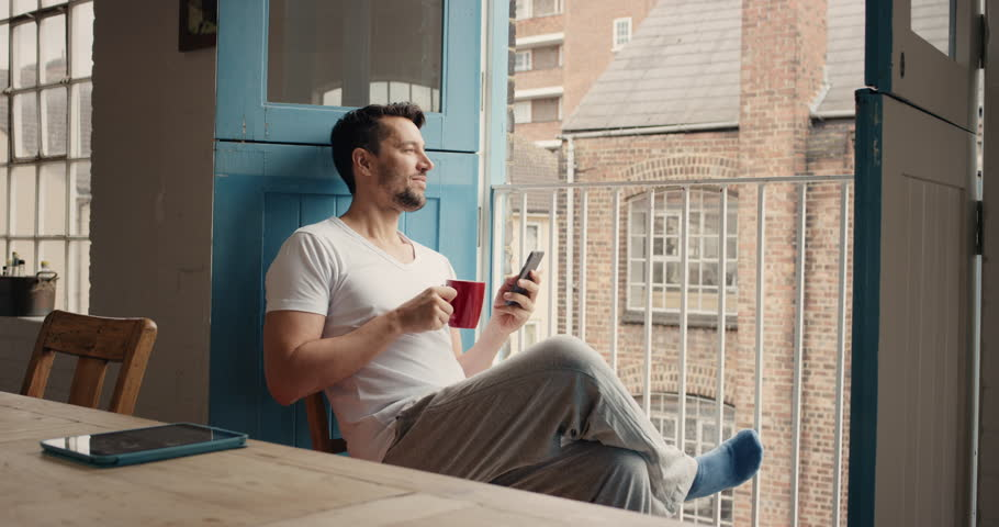 Handsome man at home drinking coffee using smartphone loft apartment in pajamas relaxing