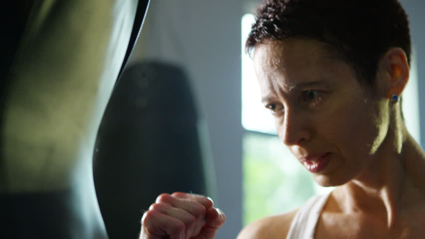4K Female martial artist or boxer training with a punch bag at the gym. Shot on RED Epic.   Shutterstock HD Video #12287105