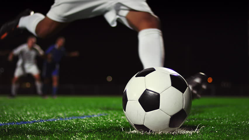 Close up of a soccer ball being kicked in slow motion at night #12304745