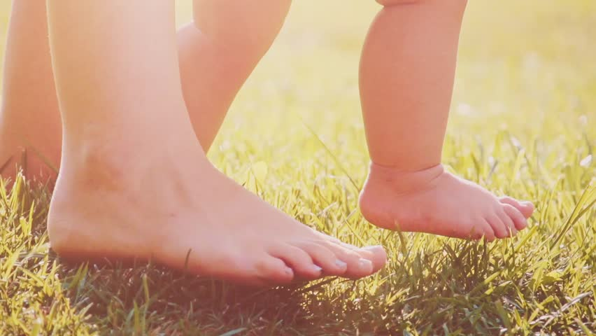 Little baby learns to walk. Close up on feet. Slow Motion 240 fps. Mother is teaching her child to do the first steps on a green grass in summer. Toddler is learning to walk outdoors on a green lawn. | Shutterstock HD Video #12311756