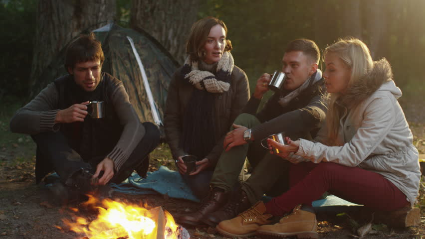 Group of people sit in a forest next to a campfire with warm drinks from thermos and talk. Shot on RED Cinema Camera in 4K (UHD).