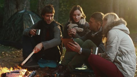 Group of men and women sit next to a campfire with drinks and use tablet in a forest. Shot on RED Cinema Camera in 4K (UHD).